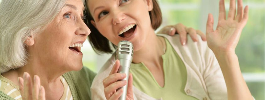Portrait of Senior woman with daughter singing on microphone at home